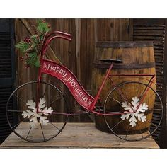 "Metal Christmas Bicycle features metal snowflake spokes, a Happy Holidays greeting, and a festive wreath on the handle bars. It measures 25"" high by 37"" long."
