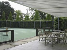 A #tennis #court with a polished concrete terrace and oak fencing with netting. Check more at www.newhampshirehomes.com