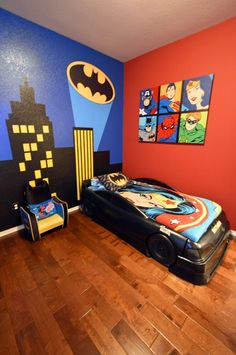 Boy's Batman Superhero themed room with Bat Signal over the city wall mural, Batmobile bed and custom canvas painting featuring Superman, Wonder Woman, Spider-Man, Captain America and The Flash [Lane Crosno Designs]