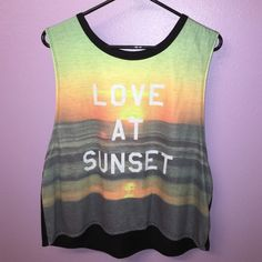 Girls muscle shirt Girls muscle shirt with love at sunset printed on the front. All black in the back and the arm holes reach down to about my stomach. Only worn once because it is too big for me. Decree Tops Muscle Tees