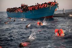 Migrants jump into the water from a crowded wooden boat as they are helped by members of an NGO during a rescue operation in the Mediterranean Sea, just north of Libya on Aug. 29, 2016.