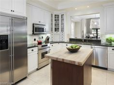 White kitchen with chopping block center island.  Olde Naples beach house on 7th Street South.  Naples, Florida