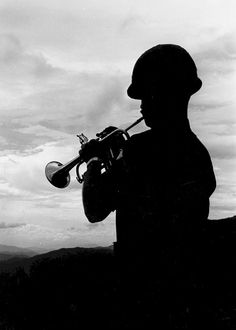 A bugler on a hill overlooking the A Shau Valley plays taps at a memorial service for the fallen soldiers of the 2nd Bn, 319th Arty., 101st Airborne Division at Camp Evans, Vietnam, 1969.