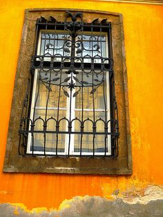 Orange decayed wall and wrought iron window. Baltic Region, Iron Windows, Heart Of Europe, Beautiful Lines, Central Europe, Facade Architecture, Budapest Hungary, Eurotrip, Window Wall