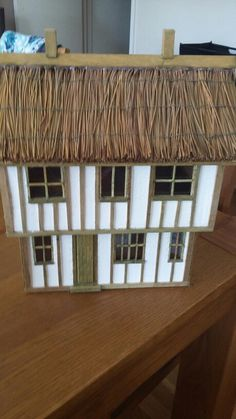 Tudor house made from cardboard boxes wooden battens glued to walls and around windows. Roof is made from pine needles for that thatched effect. Glass in the windows from acetate made to look like lead windows.