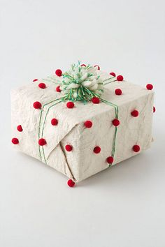 Festive gift wrap. Love the pom poms.