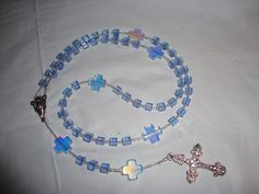 Rosary: Hail Mary: cube blue beads separated by crystal 3 seed beads; Our Father: Cross Beads separated by 6 crystal seed beads.