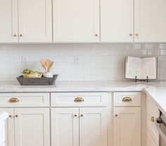 White Shaker Cabinetry With Brass Cups And Knobs By