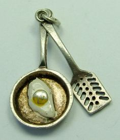 A 1960s English silver Nuvo charm of a spatula and frying pan with enamel painted fried egg, SUPERB and RARE - 45 gbp