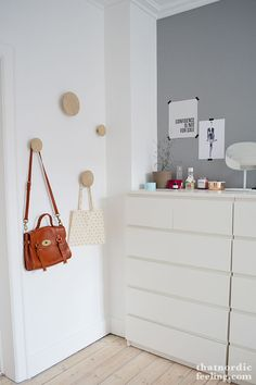 that nordic feeling bedroom - likes the knobs the purses are hanging on.