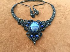 Ce merveilleux collier macramé boho chic est réalisé à partir de Lapis Lazuli (3,5cmX2,5cm). La pierre est sertie dans du fil ciré noir résistant à leau, et décoré de perles en hématite et lapis lazuli. Sa taille est ajustable dans la nuque grâce à un système de liens coulissants. Design original par BelisaMag. Depuis la plus Haute Antiquité, le Lapiz abonde en objets religieux et en bijoux confectionnés pour les grands dignitaires. Le Lapis Lazuli favorise la clairaudience et la…