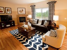 An up-to-date living room features a corner fireplace and graphic print drapes and rug. A cream, nailhead chair and lucite lamps mix it up with a chocolate brown sofa.