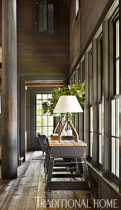 The homeowner personally reclaimed hundred-year-old wood from a plantation house and cotton gin. He then hand-planed the wood and devised a machine to create a wire-brush finish. This shows how much he loves this home!Lake House with Rustic Interiors