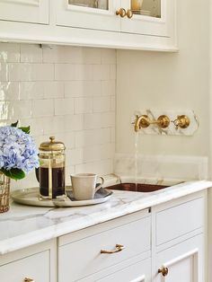 Exquisite butler's pantry features glass front upper cabinets and white lower cabinets paired with ...