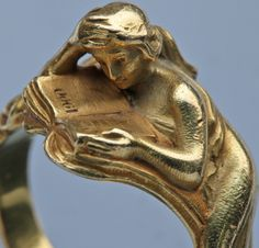 "marisadobson: By Louis Zorra (an Italian designer who worked in Paris), it depicts a reclining woman immersed in a book that reads ""Paris Art Nouveau Ring Celebrating the Paris 1900 Exhibition - Gold"
