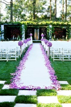 A bright wedding aisle showcases a border of purple rose petals that compliment the fresh green grass that surrounds.