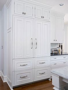Concealed beneath cabinetry panels, the fridge-freezer combo blends effortlessly with the kitchen's traditional-style cabinets.