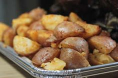 potatoes cooked on smoker in open pan.