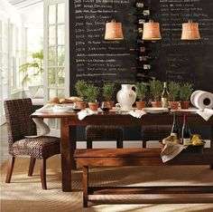 Dining room chalkboard wall, rustic table, woven chairs, rosemary