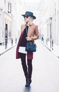 A cropped jacket is layered over a sweater and button-down shirt.