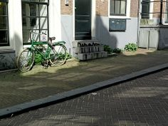 A view over the small connection-street TussenKadijken with sun and shadows on the pavements and walls, in the Spring of 2013; in Amsterdam city; urban photography Fons Heijnsbroek