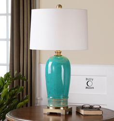 Uttermost Albertus Lamp. Ceramic base finished in a crackle blue glaze with a rust glaze and plated brushed antiqued gold details. The slightly tapered round hardback shade is a white linen fabric with light natural slubbing. Due to the nature of fired glazes on ceramic lamps, fi