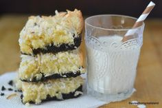 Photo of Black Bottom Coconut Squares on a napkin with a glass of milk in the background.