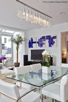 Contemporary dining room with an elegant and modern feel thanks to the white furniture, blue modern art, glass dining table and a long crystal chandelier. #modern #glass #diningroom