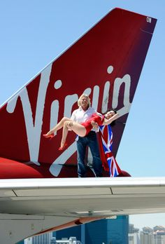 Founder and President of Virgin Group Sir Richard Branson (L) and  Dita Von Teese appear on the wing of a Virgin Atlantic