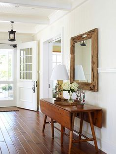 Pretty rustic wooden mirror over slim lined table. Perfect for an entry way!