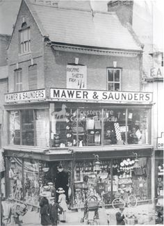 Mawer and Saunders was an ironmongery business selling hardware, seen here around 1910. They traded from the turn of the twentieth century and closed in the 1990s. Note the Edwardian ladies formal costume and the old currency used in the display on the shop window and on the advertisement for roofing sheets. This two-story shop became Chinatown, half way up the High Street and on the corner of Church Street, but is now closed and empty.