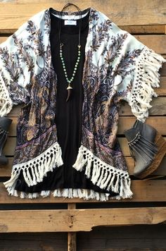 Our Angels Flying Kimono Top is a must have! It's an open front kimono style top with unique paisley print and tassels to accent the sleeves and bottom hem. Made to be loose fitted. $39