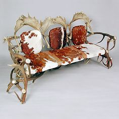 http://www.antiques-furniture-online.com Unique deer antler settee from a Black Forest chalet. This large three-seat settee fashioned from a combination of natural red and fallow deer antlers features original upholstery in vintage cowhide.
