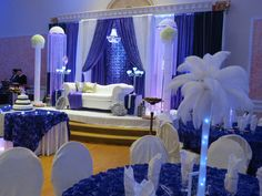 Purple and white with purple rosette, white loveseat with crystals, stage covering, crystal columns, side accent tables with crystal candelabra with built in led light.  Affordable event decor done at Chandni Gateway in Brampton www.fairytalescreationsandcatering.com