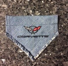 Denim embroidered dog bandana with the C5 Corvette logo and lettering. Fringy edges get softer and more fringed as washed and dried.  This is a scarf/bandana that slides over the dogs current collar.  The opening for dogs collar to slip through is 1 1/4 Extra small is 6.5 wide at top and 5 from point to top edge where collar attaches.  More sizes are available as well as custom orders.  Please allow 2 weeks for custom work.  One available now and ready to ship. More are in the process of…