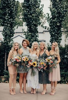 mismatched bridesmaid dresses in blush and sage with sunflower bouquets