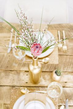 Gorgeous DIY african touch wedding flowers - gold wine bottle,  protea and any delicate filler eg bear grass or wax flower
