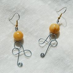 This is a pair of wire-wrapped earrings that features beads (a kind of muted yellow-orange colour) and a silver wire-wrapped design.