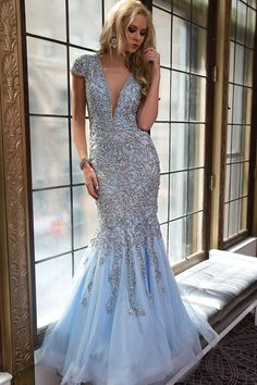 Gorgeous blue mermaid cap sleeve gown features a crystal embellished bodice and plunging neckline