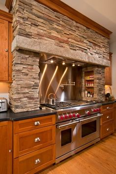 A large Wolf dual oven and range, full overlay oak cabinets and a custom masonry hearth can make anyone feel like a master chef in this open floor plan kitchen. Kitchen remodel by Teakwood Builders, Saratoga Springs, NY.