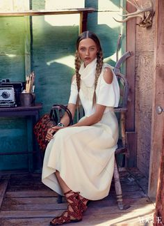 """An important element of the easygoing aesthetic is a less-constricting, looser silhouette; on these frontiers, at least, """"body-con"""" has been left in the dust. Derek Lam cream dress with crop top and shoulder cutouts ($2,990) and fringe scarf; Derek Lam, NYC. Bottega Veneta bag. Giuseppe Zanotti Design embellished sandals."""