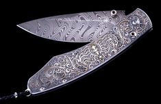 The Spearpoint 'Lace' by William Henry knives features a mesmerizing hand-engraved handle with inlaid 24K gold by Mario Terzi. The beautiful blade is hand-forged 'Boomerang' damascus steel by Chad Nichols; the one-hand button lock and the thumb stud are set with spinel.