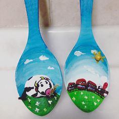 wooden spoons. a cow is watching the train. made of pepples.