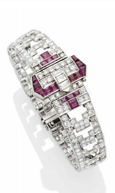 AN ART DECO RUBY AND DIAMOND BRACELET. Geometric links set with brilliant cut diamonds, centring a belt buckle design set with rubies, mounted in platinum setting, circa 1930. #ArtDeco #bracelet