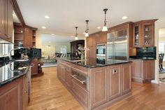 Large luxury kitchen with black granite and pecan colored wood cabinets.