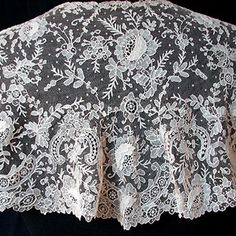 Exquisite Brussels Point De Gaze Shawl -  Circa 1860, a beautiful design and excellent quality workmanship on this superb large Brussels Point De Gaze shawl. The net ground is also handmade, always a sign of the best quality in Brussels lace. This has 34-35 roses with raised three-dimensional petals, masses of flowers, leaves, scrollwork, and scattered Point De Esprit. A beautiful example, absolutely encrusted with fine work. - Maria Niforos -