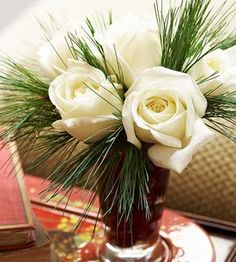 White Roses & Pine This Christmas flower arrangement is simple and sweet. Fill your favorite glass vase with cut roses and pieces of pine. For an extra merry touch, include cranberries in the vase.