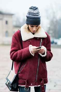Cozy winter style: oversized shearling moto jacket in burgundy and printed beanie