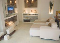 Linda sala com sofá branco em couro, porcelanato e rack também branco.