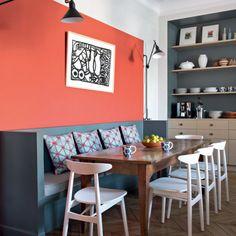 Un coin repas convivial dans la cuisine corail, turquoise et cobalt, autour de la longue table dessinée par les architectes GCG, banquette en Panbéton.